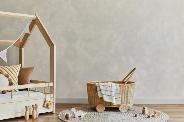 Stylowa kompozycja przytulnego skandynawskiego wnętrza pokoju dziecięcego z łóżkiem, rattanowym koszem, pluszowymi i drewnianymi zabawkami oraz tekstylnymi wiszącymi dekoracjami. ściana kreatywna, na podłodze dywan. skopiuj miejsce. szablon.