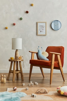 Stylowa kompozycja przytulnego skandynawskiego wnętrza pokoju dziecięcego z mocną ramą plakatową, czerwonym fotelem, elegancką lampą, pluszowymi zabawkami i wiszącymi dekoracjami. ściana kreatywna, na podłodze dywan. szablon.