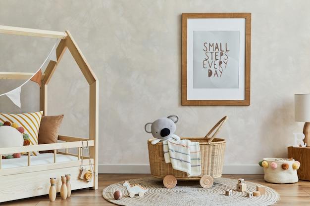 Stylowa kompozycja przytulnego wnętrza dziecięcego pokoju scandi z mocną ramą plakatową, łóżkiem, rattanowym koszem, pluszowymi i drewnianymi zabawkami oraz dekoracjami. kreatywna ściana. skopiuj miejsce. szablon.