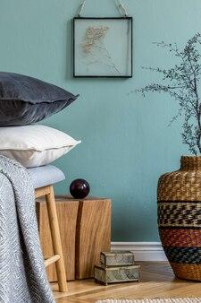 Stylowa kompozycja przytulnych detali wnętrza salonu jak drewniana kostka i wazon z suchym kwiatem oraz czarno-białe eleganckie welurowe poduszki zielone ściany parkiet podłoga