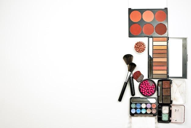 Stylowa kompozycja różnorodnych palet z produktami pudrowymi i innymi kosmetykami do makijażu