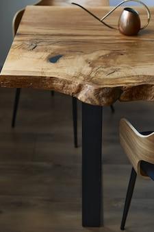 Stylowa kompozycja rzemieślniczego dębowego stołu z krzesłami, miedzianej konewki i nowoczesnej podłogi w pięknej oranżerii. szablon.