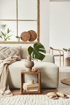 Stylowa kompozycja salonu z designerską beżową sofą, drewnianym stołkiem, tropikalnym liściem w wazonie, książką, dekoracją, meblami i eleganckimi dodatkami osobistymi.
