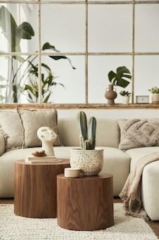 Stylowa kompozycja salonu z designerską beżową sofą, drewnianym taboretem, kaktusami, roślinami, książką, dekoracją, meblami i eleganckimi dodatkami osobistymi. nowoczesny wystrój domu. otwarta przestrzeń..