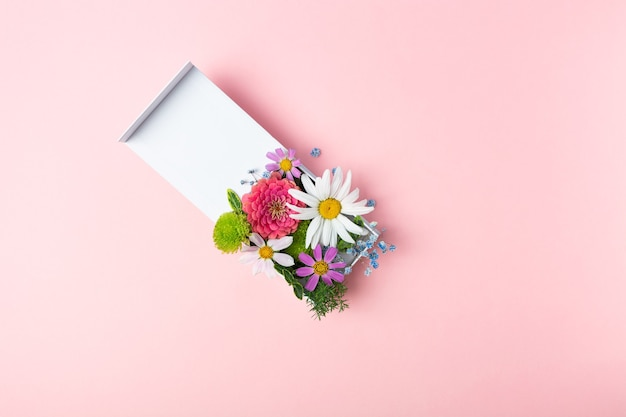 Stylowa kompozycja świeżych kwiatów w białym pudełku na różowym tle