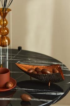 Stylowa kompozycja w fantazyjnym wnętrzu z marmurowym stolikiem kawowym, designerską tacą z orzechami i filiżanką kawy w nowoczesnym wystroju domu. detale..