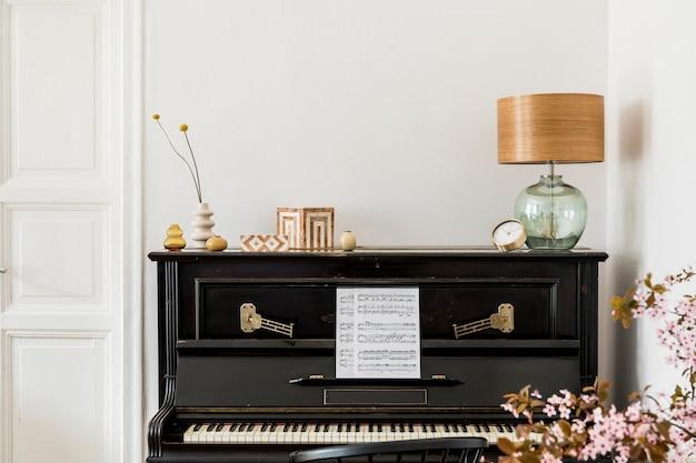 Stylowa kompozycja we wnętrzu salonu z czarnym fortepianem, suszonymi kwiatami w wazonie, złotym zegarem, designerską lampą, pudełkami, przestrzenią do kopiowania i eleganckimi dodatkami w nowoczesnym wystroju domu.