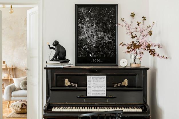 Stylowa kompozycja we wnętrzu salonu z czarnym pianinem, makietą mapy plakatowej, suszonymi kwiatami, białym zegarem, designerską lampą i eleganckimi presonalnymi dodatkami w nowoczesnym wystroju domu.