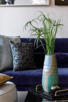 Stylowa kompozycja we wnętrzu salonu z szarą pufą, aksamitną sofą, poduszkami, stolikiem kawowym, tropikalnym liściem w wazonie, marmurową tacą w nowoczesnej koncepcji