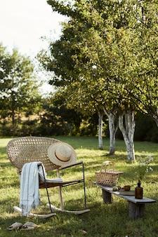 Stylowa kompozycja wiejskiego ogrodu z designerskim rattanowym fotelem, drewnianą ławką, kratą, jedzeniem, napojami i eleganckimi dodatkami. wiele kolorowych kwiatów. letni nastrój.