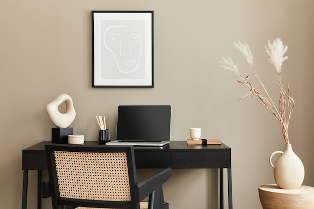 Stylowa kompozycja wnętrza domowego biura z czarnym drewnianym biurkiem, krzesłem, suszonym kwiatem w wazonie, laptopem, makieta plakatowa, filiżanką kawy, zegarem i eleganckimi akcesoriami biurowymi. szablon.