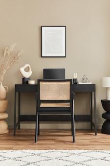 Stylowa kompozycja wnętrza domowego biura z czarnym drewnianym biurkiem, krzesłem, suszonym kwiatkiem w wazonie, laptopem, makietową ramką plakatową, filiżanką kawy, zegarem i eleganckimi akcesoriami biurowymi