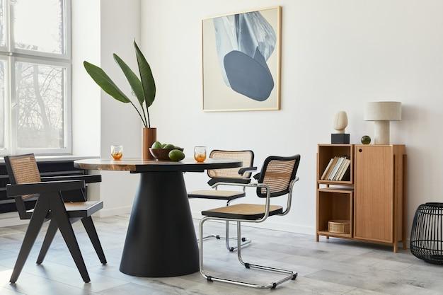 Stylowa kompozycja wnętrza jadalni z designerskim stołem, nowoczesnymi krzesłami, dekoracją, tropikalnym liściem w wazonie, owocami, regałem, abstrakcyjnymi obrazami i eleganckimi dodatkami w wystroju domu.