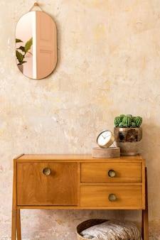 Stylowa kompozycja wnętrza salonu w stylu retro z drewnianą komodą vintage, złotym różowym lustrem, rośliną, rattanowym koszem, pledem, dekoracją i eleganckimi dodatkami osobistymi w wystroju domu wabi sabi.