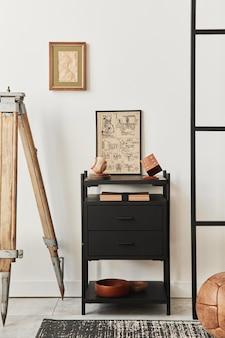 Stylowa kompozycja wnętrza salonu z brązową drewnianą ramą, książką, czarną półką, dekoracją i eleganckimi dodatkami... biała ściana.