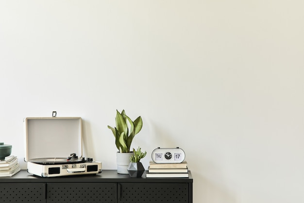Stylowa kompozycja wnętrza salonu z designerską czarną komodą, roślinami, książką, magnetofonem, dekoracją i eleganckimi dodatkami osobistymi. skopiuj miejsce. nowoczesny wystrój domu.