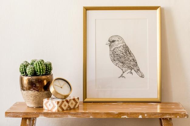 Stylowa kompozycja wnętrza salonu ze złotą ramą, drewnianą ławką, złotym zegarem, pudełkami, kaktusami, białą ścianą i eleganckimi dodatkami osobistymi w nowoczesnym wystroju domu.