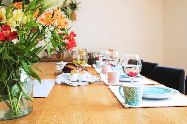 Stylowa kompozycja wystroju wnętrza jadalni z talerzami, filiżankami, szklankami i jedzeniem. słoneczny i jasny pokój, jasne kolory. styl śródziemnomorski.