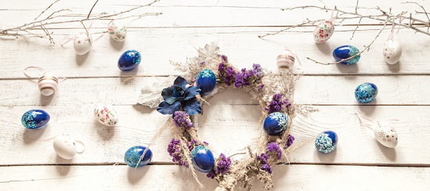 Stylowa kompozycja z wieńcem wielkanocnym i modnymi jajkami w kolorze niebieskim.