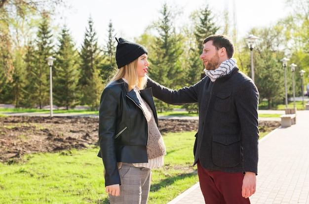 Stylowa koncepcja ciąży - portret para męża i żony biodrówki w modne ubrania spaceru w parku miejskim.