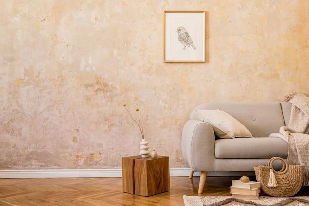 Stylowa koncepcja wnętrza salonu z designerską szarą sofą, makietą ramki na zdjęcia, suszonym kwiatem, drewnianą kostką, książkami, dywanem, kobiecą torebką, poduszką, kratą i eleganckimi akcesoriami w wystroju domu.
