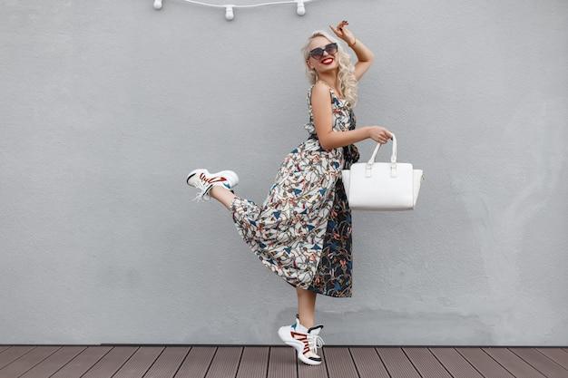 Stylowa ładna hipsterka modelka w okularach przeciwsłonecznych z białą torbą w sukience we wzory i stylowe trampki skacze w pobliżu szarej ściany. szczęśliwy styl życia na zakupy