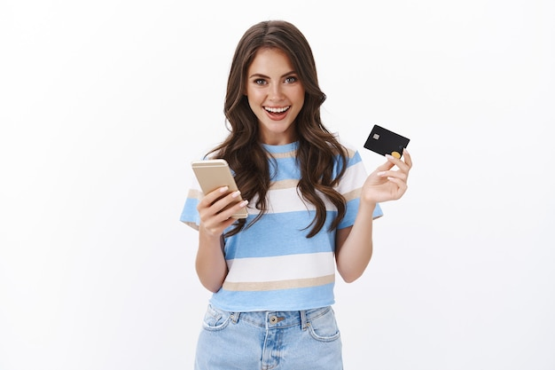 Stylowa, ładna kobieta robiąca zamówienie, płacąca za zakupy online kartą kredytową, uśmiechająca się radośnie smartfon, wyjaśniająca, jak łatwo zrobić zakupy w internecie, biała ściana