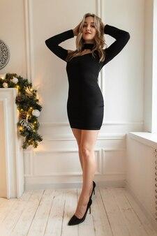 Stylowa ładna młoda dziewczyna z fryzurą w modnej eleganckiej czarnej sukience z seksownymi nogami pozuje przy białej ścianie