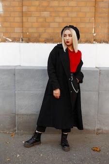 Stylowa ładna młoda kobieta blondynka w długim czarnym płaszczu vintage w spodniach w czerwonej koszuli w berecie w skórzanych butach odpoczywa stojąc obok ściany z cegły w słoneczny jesienny dzień