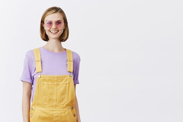 Stylowa ładna młoda kobieta w okularach przeciwsłonecznych i letnich ubraniach wygląda beztrosko, uśmiechając się szczęśliwy
