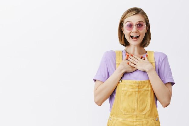 Stylowa ładna młoda kobieta w okularach przeciwsłonecznych i letnich ubraniach wyglądająca beztrosko, obejmująca ręce i wyglądająca na podekscytowaną, ciesząc się świetnymi wiadomościami