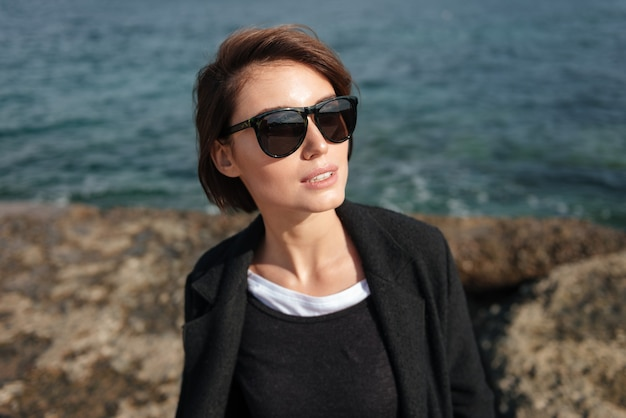 Stylowa ładna młoda kobieta w okularach przeciwsłonecznych stojących w pobliżu morza