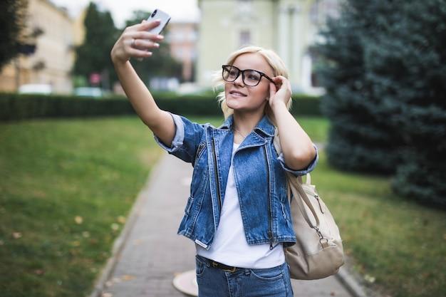 Stylowa, ładna moda blondynka kobieta w dżinsach suite sprawia, że selfie na swoim telefonie w mieście w godzinach porannych