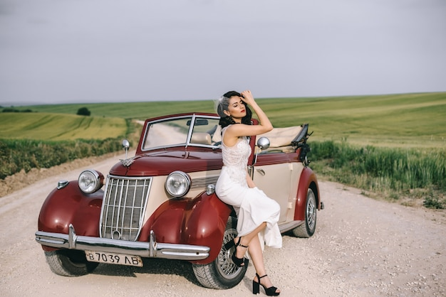 Stylowa ładna panna młoda siedzi na czerwonym samochodzie retro na polnej drodze