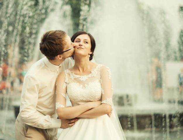 Stylowa luksusowa panna młoda i elegancki pan młody, przytulający się z czułością, na przestrzeni starego miasta lwowa