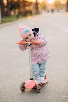 Stylowa mała dziewczynka jedzie hulajnoga w parku przy zmierzchem