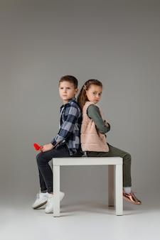 Stylowa mała para dziecko dziewczynka i chłopiec z czerwonymi sercami na kij w modne ubrania siedząc razem