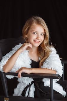 Stylowa mała uśmiechnięta dziewczyna pozuje w białym stroju na białym tle na ścianie czarnej pracowni