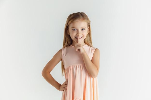 Stylowa mała uśmiechnięta dziewczyna pozuje w sukience na białym tle na białej przestrzeni. kaukaski blond modelka. ludzkie emocje, wyraz twarzy, dzieciństwo
