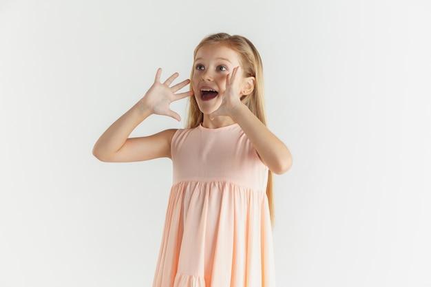 Stylowa mała uśmiechnięta dziewczyna pozuje w sukience na białym tle na białej ścianie. kaukaski blond modelka. ludzkie emocje, wyraz twarzy, dzieciństwo. dzwonię, zdumiony, zdziwiony.