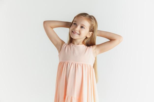 Stylowa mała uśmiechnięta dziewczyna pozuje w sukience na białym tle na białej ścianie. kaukaski blond modelka. ludzkie emocje, wyraz twarzy, dzieciństwo. odpoczynek i marzenie.