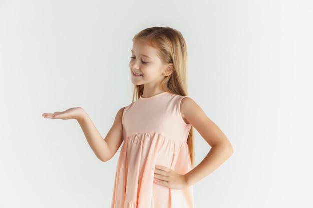 Stylowa mała uśmiechnięta dziewczyna pozuje w sukience na białym tle na białej ścianie. kaukaski blond modelka. ludzkie emocje, wyraz twarzy, dzieciństwo. pokazywanie na pustej spacji.