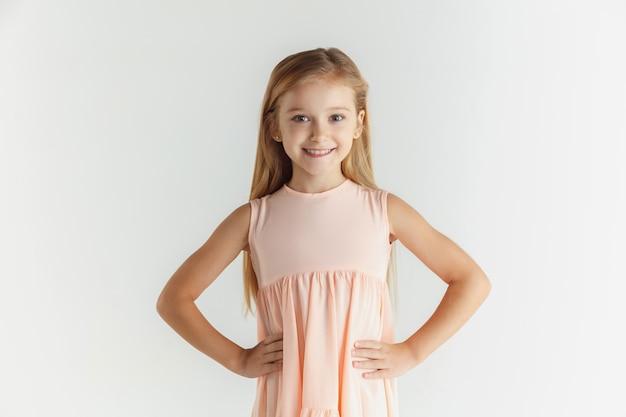 Stylowa mała uśmiechnięta dziewczyna pozuje w sukience na białym tle na białej ścianie. kaukaski blond modelka. ludzkie emocje, wyraz twarzy, dzieciństwo. uśmiechnięty, trzymając się za ręce na pasku.