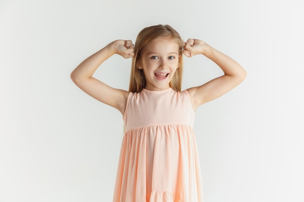 Stylowa mała uśmiechnięta dziewczyna pozuje w sukience na białym tle na białej ścianie. kaukaski blond modelka. ludzkie emocje, wyraz twarzy, dzieciństwo. uśmiechnięty, wygrywający, świętujący.