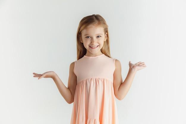 Stylowa mała uśmiechnięta dziewczyna pozuje w sukience na białym tle na białej ścianie. kaukaski blond modelka. ludzkie emocje, wyraz twarzy, dzieciństwo. uśmiechnięty, zdumiony, zdumiony.
