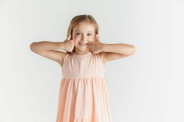 Stylowa mała uśmiechnięta dziewczyna pozuje w sukience na białym tle na białej ścianie. kaukaski blond modelka. ludzkie emocje, wyraz twarzy, dzieciństwo. wygląda spokojnie, pokazując znak miłego.