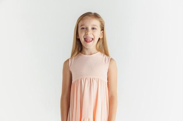 Stylowa mała uśmiechnięta dziewczyna pozuje w sukience na białym tle na białej ścianie. kaukaski blond modelka. ludzkie emocje, wyraz twarzy, dzieciństwo.
