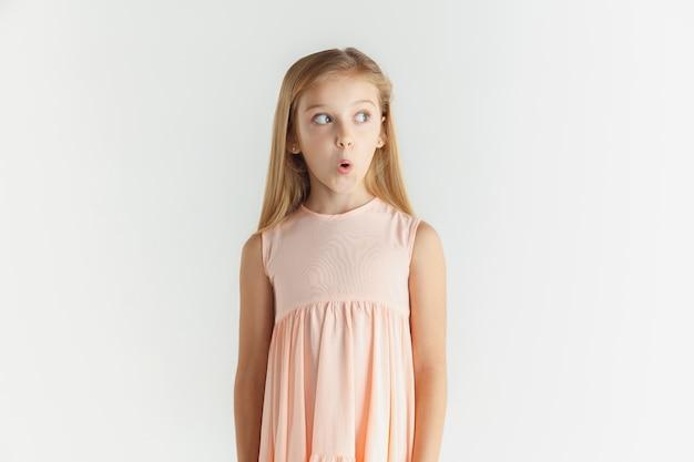 Stylowa mała uśmiechnięta dziewczyna pozuje w sukience na białym tle na białej ścianie. kaukaski modelka. ludzkie emocje, wyraz twarzy, dzieciństwo. zdziwiony, zdumiony, zszokowany. patrząc z boku.