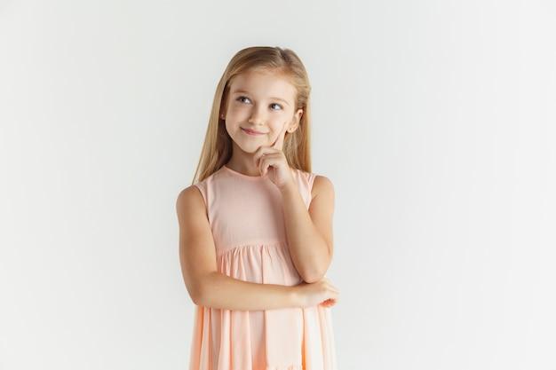 Stylowa mała uśmiechnięta dziewczyna pozuje w sukience na białym tle na tle białego studia. kaukaski blond modelka. ludzkie emocje, wyraz twarzy, dzieciństwo. myślenie lub śnienie,