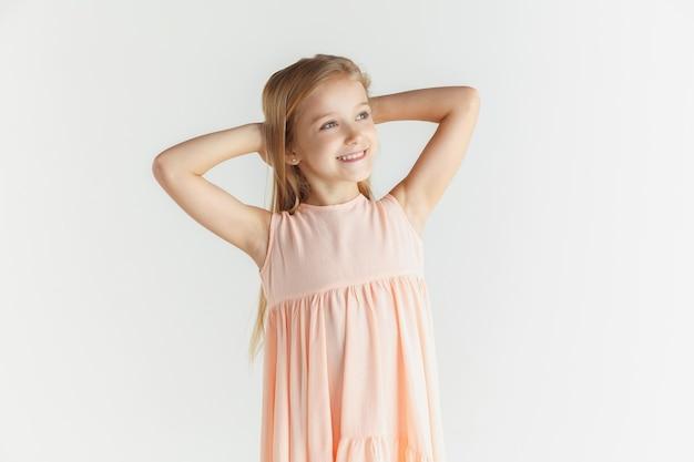 Stylowa mała uśmiechnięta dziewczyna pozuje w sukience na białym tle na tle białego studia. kaukaski blond modelka. ludzkie emocje, wyraz twarzy, dzieciństwo. odpoczynek i marzenie.